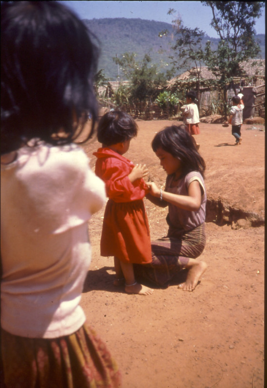 難民キャンプにて、小さな子のお手伝いをする少女